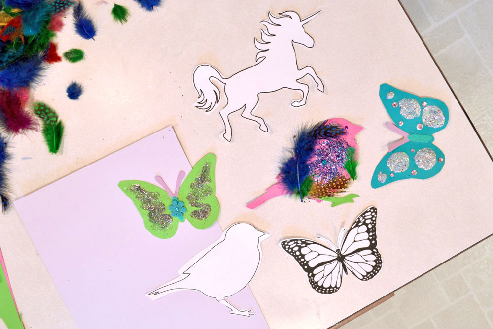Colorful paper cutouts and unicorn and butterfly crafts for kids